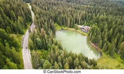 Beautiful Chalet along the lake in a wonderful mountain forest, aerial view.