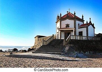 Beautiful chapel in the sea called Senhor da Pedra in Miramar beach in the south of Porto in the north of Portugal