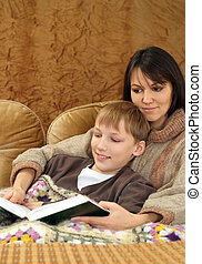Beautiful charming Caucasian mother with her son reading a book