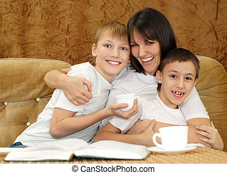 Beautiful charming mother and sons sitting on a brown ...