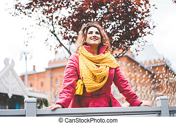 Beautiful cheerful curly red-haired woman against the background of holiday town