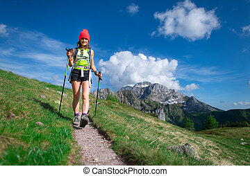 Beautiful cheerful girl during a hike with poles in the mountains