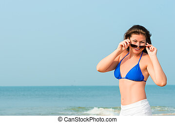 beautiful cheerful girl posing against a background of the sea