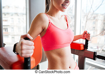 Beautiful cheerful sportswoman training in gym