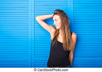 beautiful cheerful teen girl in black top over blue background