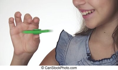 Beautiful cheerful teen girl playing with green fidget...