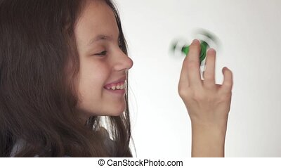 Beautiful cheerful teen girl playing with green fidget...
