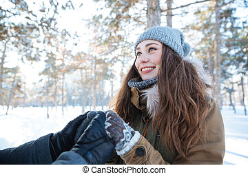 Beautiful cheerful woman holding hands with her boyfriend