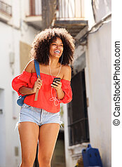 Beautiful cheerful woman standing with smart phone and earphones