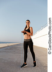 Beautiful cheerful woman with jumping rope training isolated