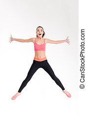 Beautiful cheerful young sportswoman jumping in the air