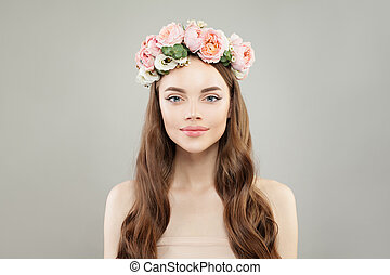 Beautiful cheerful young woman with clear healthy skin, shiny hair and roses flowers