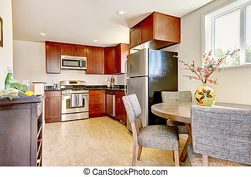 Beautiful cherry kitchen with stain steal apliances.