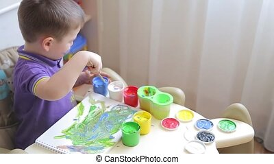 Beautiful child draws with colored paints while sitting at table