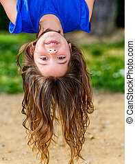 beautiful child hanging upside with greenery in the ...