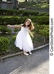 Beautiful child in white dress playing outdoors