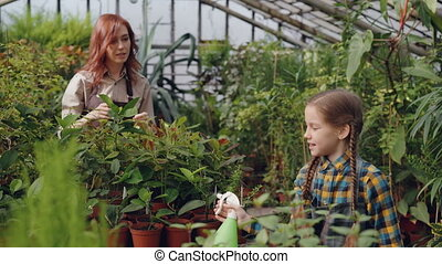 Beautiful child is sprinkling water on pot plants under...