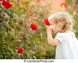 Beautiful child smelling rose against spring flowery ...