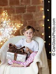 Beautiful child with a christmas gift in pajamas sitting on the chair