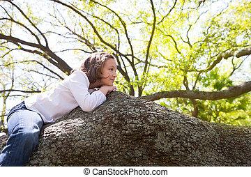 Beautiful children kid girl resting lying on a tree