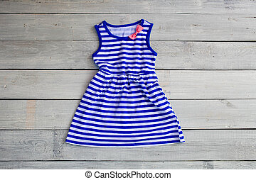 Beautiful children's dress for the girl, in sea style on a white wooden background