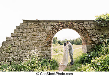 beautiful chinese couple, woman in luxury wedding dress and man in gray suit, standing in old vintage stone arch, outdoors near the castle