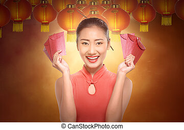 Beautiful chinese woman in a traditional dress holding red envelopes
