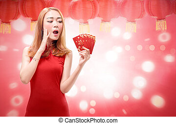 Beautiful chinese woman with traditional dress holding angpao