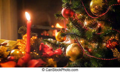 Beautiful christmas background with burning candles, fireplace and decorated Christmas tree