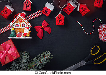 Beautiful christmas decor baubles and scissors on dark black background. Flat lay design. Copy Space. Horizontal.