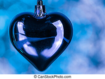Beautiful Christmas decorations in the shape of heart on blue texture in foreground