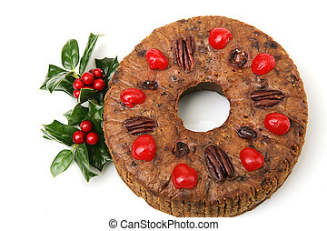 Beautiful Christmas fruitcake topped with cherries and pecans, garnished with colorful holly. Isolated on white.