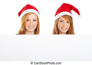 beautiful Christmas girls holding a white board