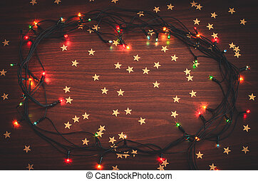 Beautiful christmas glowing garland with golden star confetti on the wooden table top view toned background copy space