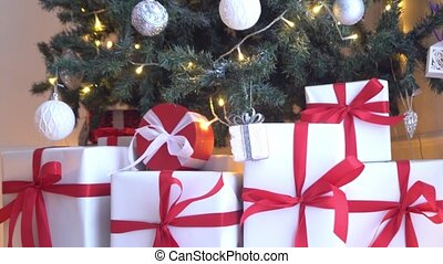 Beautiful Christmas tree decorated with balls and lights. Present boxes, gifts in front.