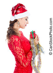 Beautiful christmas woman is holding red gift in studio.