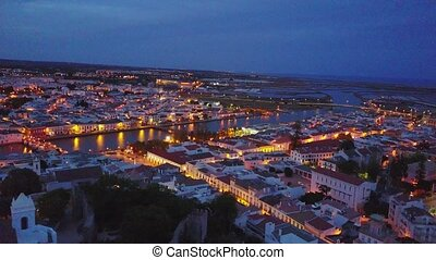 Beautiful city center of Tavira by Gilao river at night,...