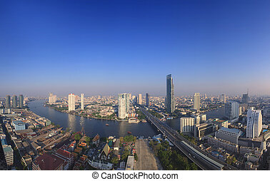 beautiful city scape from sky scrapper in heart of bangkok capital of thailand ,with important office building and chaophraya river curve against clear and bright blue sky