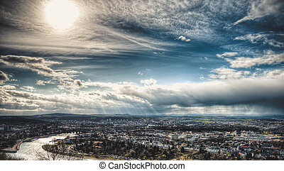 Beautiful city view with blue sky, sun and rain clouds.