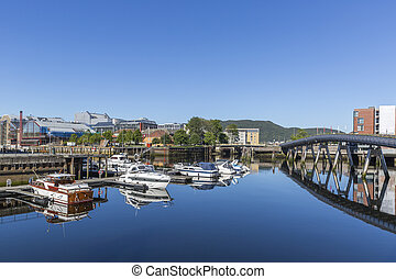 Beautiful cityscape of Trondheim with yachts and pedestrian bridge