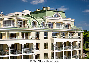 classic building with arcs om balconies and green metal roof...