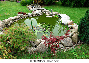 Beautiful classical design garden fish pond in a well cared backyard gardening background