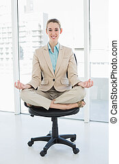 Beautiful classy woman sitting in lotus position on her...