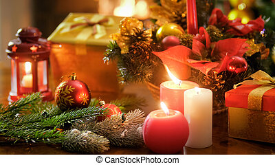 Beautiful closeup photo of burning candles and Christmas decorations on wooden table