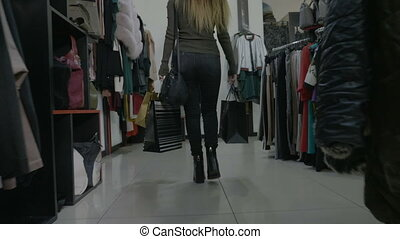 Beautiful college girl walking in high heels holding shopping bags in a clothing store mall