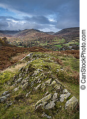 Beautiful colorful Autumn Fall landscape image of view from Loughrigg Brow towards mountains in distance with dramatic sky