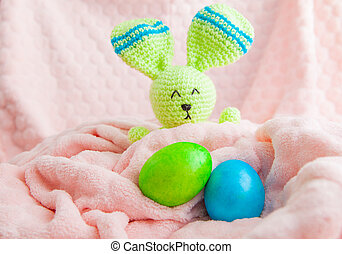 Beautiful colorful easter eggs and bunny toy. Easter concept on a soft plaid