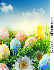 Beautiful colorful eggs in spring grass meadow over blue sky