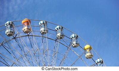 Beautiful colorful ferris wheel against blue sky at...