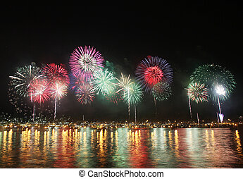 Beautiful colorful fireworks reflect on sea water